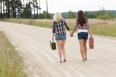 Walking friends on road back view Royalty Free Stock Image