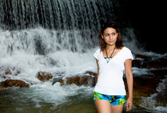 Walking in front of a water fall. Young beautiful woman in front of a water fall Royalty Free Stock Images