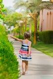 Walking girl. Girl walking along the green bush Stock Photos