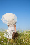 Walking girl in a flowery meadow. Blue sky concept background fo Royalty Free Stock Photo