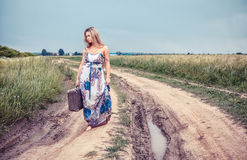 Walking girl with old suitcase on the road Royalty Free Stock Photos