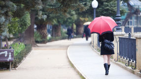 Walking girl under rain Stock Photos