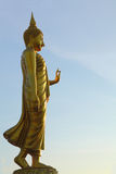 Walking golden Buddha statue Stock Images