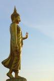 Walking golden Buddha statue Stock Images
