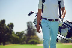 Walking golf course. Golf player walking and carrying bag on course during summer game golfing Stock Photo