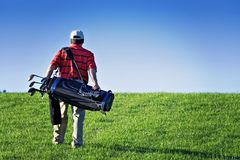 Walking Golfer. A male golfer walks the golf course - carrying bag of clubs and equipment.  Lomo effect Royalty Free Stock Photos