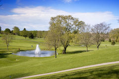 Walking Golfers By The Fountain. Walking golfers enjoy a fine day for golf at a Wisconsin golf course. Steep cart path in foreground Royalty Free Stock Images