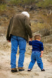 Walking With Grandpa. A very young boy hiking with his grandfather. The two are heading up a slight hill in the desert and look to be walking cautiously. Grandpa Stock Photos