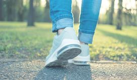 Walking in gray running shoes, back to camera. Walking in gray running shoes good for everyday wearing, blue jeans, back to camera royalty free stock images