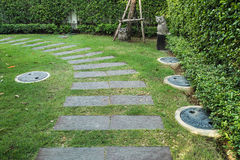 Walking through the green garden. The footpath is set as curve toward the green grass garden royalty free stock photography