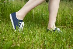 Walking on green grass in sport shoes stock image