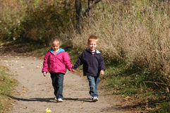 Walking Hand In Hand. Two children – twin brother and sister – walk on a path through a wooded area on a warm, autumn afternoon Royalty Free Stock Photos