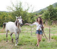 Walking with her horse Stock Image