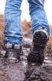 Walking hiking shoes on a muddy terrain. With legs wearing blue jeans Stock Photo