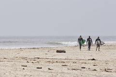 Walking home. Three people walking along the shore carrying their surfboards Stock Images