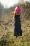 Walking home. Girl with pink hair walking home on the train tracks wearing a black party-dress Stock Photo