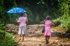 Walking home on the rocky path. Mother walking home with her daughters on a rocky trail between Maroantsetra and Antalaha in Madagascar Royalty Free Stock Photography
