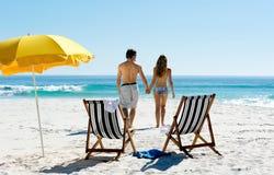 Walking honeymoon couple. Tropical summer beach holiday couple walk towards the ocean holding hands while on honeymoon vacation Stock Photo