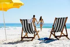 Walking honeymoon couple. Tropical summer beach holiday couple walk towards the ocean holding hands while on honeymoon vacation Stock Image