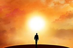 Walking on the horizon. A man is walking in the horizon towards a bright sunlight Royalty Free Stock Photos
