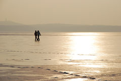 Two persons walking on ice, sunset light. A winter stroll on a frozen lake. Two people walking on ice, winter sunset royalty free stock images