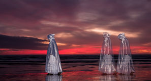 Walking Jesus Sundown. Jesus Christ and two other transparent people walking along a beach at sunset stock illustration