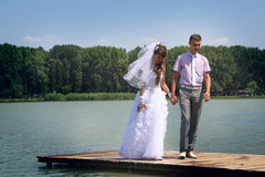 Walking at the jetty. A happy newly-married couple on river jetty Stock Photography