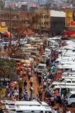 Walking through Kampala Taxi Park. KAMPALA, UGANDA - SEPTEMBER 28, 2012. People walk through the taxi park going amongst their business in Kampala, Uganda on stock photo