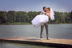 Walking and kissing. The groom holds the bride on hands. A happy newly-married couple on river jetty Stock Photos