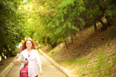 A walking lady. An openly smiling lady walking along a park path with a bottle of water, cell phone and sunglasses Royalty Free Stock Images