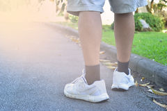 Walking. Low angle rear sport shoes walking workout power walking outdoors in public park , background and open space around him Royalty Free Stock Photo