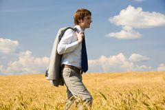 Walking man. Handsome businessman walking in wheat field Royalty Free Stock Photo