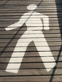 Walking man. White painted man over wooden surface Stock Photo