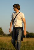 Walking man. Young man in jeans walking Royalty Free Stock Photography