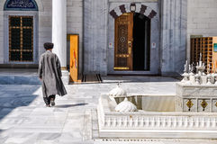 Walking man in Ashgabat. Photo of native man in long coat walking away to building made of stone and marble in Ashgabat in Turkmenistan royalty free stock photo