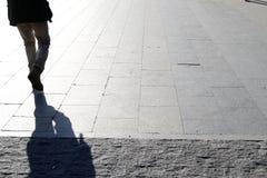 Walking man, from backside. Shadow stock photo