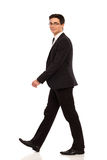 Walking man in black suit. Smiling man walking in black suit. Full length studio shot isolated on white Stock Image