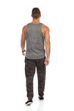 Walking Man In Camo Sweat Pants Rear View. Fit man walking in tracksuit pants with camo, gray tank top and black sneakers. Rear view. Full length studio shot stock photography