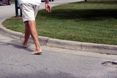Walking. A man walking on the edge of a cement road in bare feet Royalty Free Stock Photos