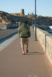 Walking man with enormous backpack Royalty Free Stock Photography