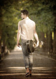 Walking man with a guitar. Young guitarist walking away along the boulevard, view from back Royalty Free Stock Photo