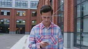 Walking Man Messaging on Smartphone, Typing, Front View. Creative designer , businessman stock video