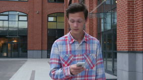 Walking Man Typing Message on Smartphone, Front view stock footage
