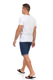 Walking Man In White T-shirt And Shorts. Rear Side View Stock Images
