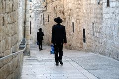 Walking men in Jewish Quarter of Jerusalem. Two unrecognized religious jewish men walking down the street in Old City of Jerusalem Stock Image