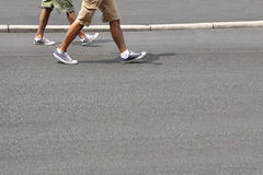Walking men. Two young men in running shoes, walking down the street Stock Photo