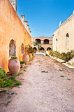 Walking in monastery. The courtyard of Arkadi Monastery with different flowers in amphoras, Crete Royalty Free Stock Photography