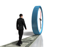 Walking on money way following rolling clock Stock Photos