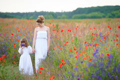 Walking mother and daughter with flowers. Summer day walk across Stock Images