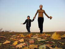 Walking mother with son on autumn leaves. Running mother with son on autumn leaves sundown royalty free stock image